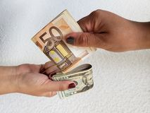 Hands of two women exchanging euro banknotes and dollar bills. Backdrop for announcements of trading and exchange, bank and commerce, background with cash and royalty free stock image