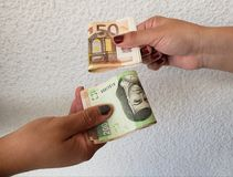 Hands of two women exchanging euro banknotes and mexican banknotes. Backdrop for announcements of trading and exchange, bank and commerce, background with cash royalty free stock photo