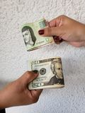 hands of two women exchanging mexican banknotes and american dollars bills royalty free stock photos
