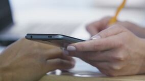 Hands of two women working on project together, checking data on smartphone. Stock footage stock video footage