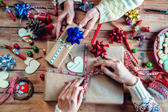 Hands of two women wrapping Christmas gifts Stock Photos