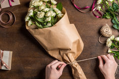 Hands tying rope on bouquet Stock Photo