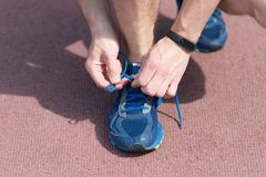 Hands tying shoelaces on sneaker, running surface background. Hands of sportsman with pedometer tying shoelaces on. Sporty sneaker. Running equipment concept Royalty Free Stock Images
