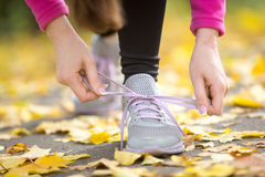 Hands tying trainers shoelaces on the autumn pave. Full of yellow leaves. Concept photo, horizontal, closeup Royalty Free Stock Photos