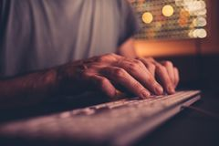 Hands type computer keyboard. Man using desktop pc in home office low light interior, selective focus stock images