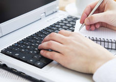 Hands Typing on Computer Keyboard and Taking Notes at Office Royalty Free Stock Photos