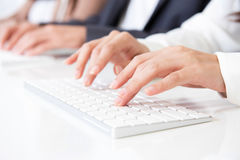 Hands typing on computer keyboards. Hands typing on white computer keyboards Stock Photos