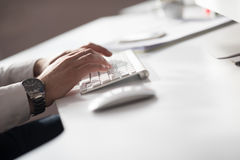 Hands typing on desktop computer. Keyboard in modern bright office interior royalty free stock image