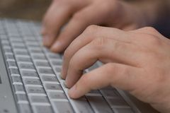 Typing. Hands on a typing on a keyboard Royalty Free Stock Photos
