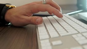 Hands typing on the keyboard. Hands typing on computer keyboard in the office on the brown table stock footage