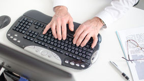 Hands typing on a keyboard Stock Photography