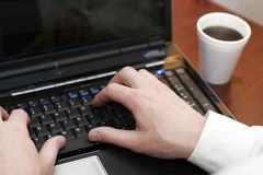 Hands typing on laptop. Image of hands typing on laptop with cup of coffee beside it stock image
