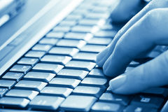 Hands typing on laptop. Man hands typing on laptop keyboard blue toned Royalty Free Stock Images