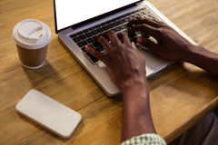 Hands typing on a laptop. In cafeteria royalty free stock photo