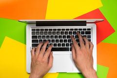 Hands typing on laptop on colorful paper. Top view flat lay.  royalty free stock photo