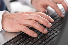 Hands typing on laptop computer Stock Photos