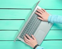 Hands are typing on the laptop keyboard on a blue wooden table. The concept of freelancing, work on the Internet. Top view. Copy space stock photo