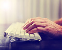 Hands typing on laptop keyboard toned with a retro vintage insta Royalty Free Stock Photos