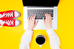 Hands typing on laptop near cup of coffee and gumshoes Royalty Free Stock Photo