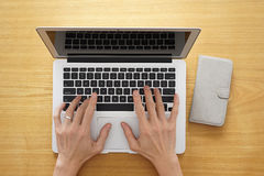 Hands typing laptop on a wooden table top Stock Photography