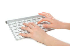 Hands typing on the remote wireless computer keyboard Stock Photos