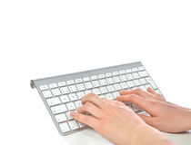 Hands typing on the remote wireless computer keyboard in an offi Stock Photos