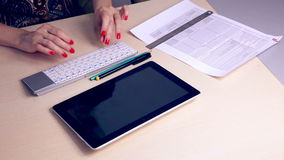 Hands typing on tablet financial information. stock footage