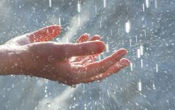 Hands under water drops. Female hands under falling clean water drops Stock Photography