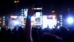 Hands of unidentified people with mobile smart phone recording video in music concert festival.  stock video footage