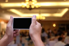 Hands of unidentified people taking photo of dinner party with mobile smart phone with blank screen stock photography