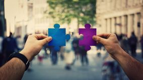 Hands unite puzzle jigsaw pieces. Two hands holding different colored puzzle pieces, unite jigsaw over a crowded street background. Business solutions, success royalty free stock image