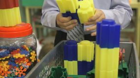 Hands of an unknown boy playing with building kit stock footage
