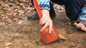 Unknown child playing with sand in sandbox. Hands of unknown child digging and playing with sand in sandbox and learning how to make shapes in an amusement park stock footage