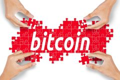 Unknown people arranging puzzle with bitcoin word Stock Image