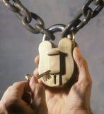 Hands unlocking old brass lock Royalty Free Stock Photos