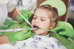 Hands of unrecognizable pediatric dentist and assistant making examination procedure for smiling cute little girl royalty free stock image