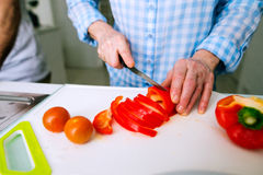 Hands of unrecognizable senior woman cutting red pepper. Royalty Free Stock Photography