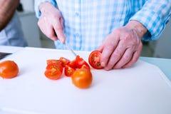 Hands of unrecognizable senior woman cutting tomatoes. Preparing Stock Photos