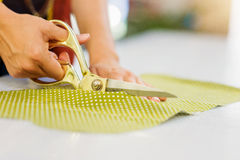 Hands of unrecognizable tailor woman cutting fabric with scissor Royalty Free Stock Images