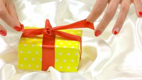Hands untie gift box, slow motion. Well-groomed hands of young woman unpacking box wirth gift close up. Sensuality and romance stock video