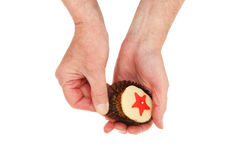 Hands unwrapping a cup cake. Male hands unwrapping a cup cake isolatewd against white Royalty Free Stock Images