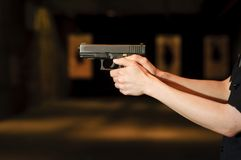 Hands up. A police officer aiming her gun at the firing range Stock Image