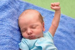 Hands Up!. Sleepy baby with fist punching the air Royalty Free Stock Photography