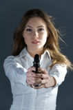 Hands up!. Beautiful woman pointing with a pistol at you, focus on pistol royalty free stock photo
