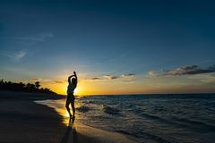 Hands up woman posing on the beach with beautiful sunset sky, clouds background. Free space for text. Cuba Varadero Yoga stock image