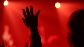 Hands up in worship during a church service. Silhouette of hands Hands up in worship during a church service with red background out of focus stock video