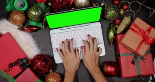 Hands use laptop between Christmas ornaments stock video footage