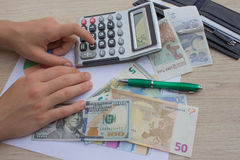 Hands using calculator and calculate money in home office. Counting money, finance, business stock image
