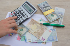 Hands using calculator and calculate money in home office. Counting money, finance, business royalty free stock image