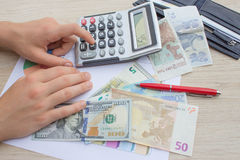 Hands using calculator and calculate money in home office. Counting money, finance, business stock photos